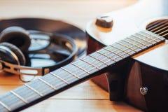 Chitarra classica con le cuffie su un fondo di legno Fotografia Stock Libera da Diritti