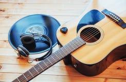 Chitarra classica con le cuffie su un fondo di legno Immagine Stock
