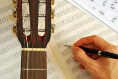 Chitarra con musica componente della mano sul manoscritto immagini stock