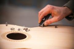 Chitarra-creatore professionale serio che lavora con la chitarra non finita all'officina Fotografie Stock Libere da Diritti