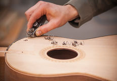 Chitarra-creatore professionale serio che lavora con la chitarra non finita all'officina Immagini Stock Libere da Diritti