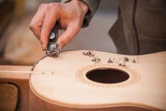 Chitarra-creatore professionale serio che lavora con la chitarra non finita all'officina Fotografia Stock Libera da Diritti