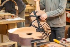 Chitarra-creatore professionale serio che lavora con la chitarra non finita all'officina Fotografia Stock