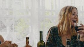 Chitarra del gioco dell'uomo sul terrazzo della casa di campagna Vino della bevanda della ragazza Amici alla tavola stock footage