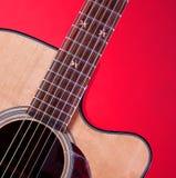 Chitarra di Acustic isolata su colore rosso Fotografia Stock Libera da Diritti