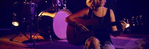 Chitarra di pratica femminile mentre sedendosi in scena Fotografia Stock