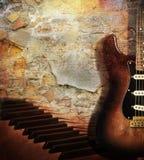 Chitarra e piano sul muro di mattoni Fotografia Stock Libera da Diritti
