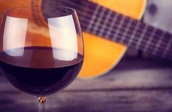 Chitarra e vino su una tavola di legno Fotografia Stock Libera da Diritti