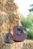 Chitarra e violino che riposano sulla divisione nei campi, w della paglia Immagine Stock