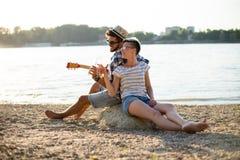 Chitarra ed alcool, romanzeschi sulla spiaggia Immagine Stock Libera da Diritti