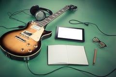 Chitarra elettrica con il blocco note e vecchia macchina fotografica su fondo verde Fotografia Stock