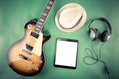 Chitarra elettrica con una compressa, un cappello e le cuffie su un fondo verde Retro immagine filtrata Immagini Stock