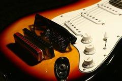 Chitarra elettrica d'annata, armonica, occhiali da sole su fondo nero Immagini Stock Libere da Diritti
