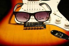 Chitarra elettrica d'annata con gli occhiali da sole su fondo nero Immagini Stock