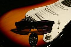 Chitarra elettrica d'annata con gli occhiali da sole su fondo nero Fotografia Stock