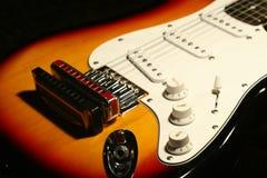 Chitarra elettrica d'annata con l'armonica su fondo nero fotografie stock libere da diritti