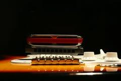 Chitarra elettrica d'annata con l'armonica su fondo nero immagine stock
