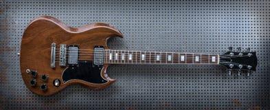 Chitarra elettrica di Brown sul fondo del metallo immagini stock libere da diritti