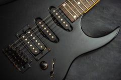 Chitarra elettrica nera sul pavimento nero del cemento fotografia stock libera da diritti