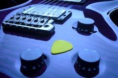 Chitarra elettrica porpora con la scelta gialla Fotografie Stock