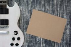 Chitarra elettrica su fondo grigio di legno, foglio di carta Fotografia Stock