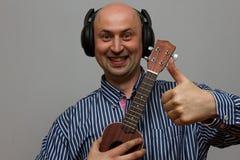 Chitarra palying delle ukulele dell'uomo felice con le cuffie Fotografie Stock Libere da Diritti