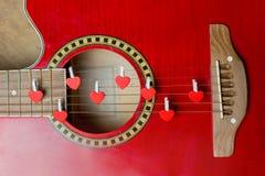 Chitarra rossa con i cuori, note di amore sulle corde Fotografia Stock