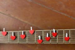 Chitarra rossa con i cuori, note di amore sulle corde Immagini Stock