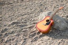 Chitarra su Pebble Beach, pendente contro una pietra Immagini Stock Libere da Diritti