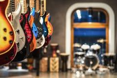 Chitarre, vetrina con le chitarre che appendono in una fila fotografia stock libera da diritti