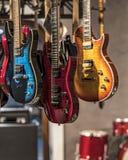 Chitarre, vetrina con le chitarre che appendono in una fila fotografia stock