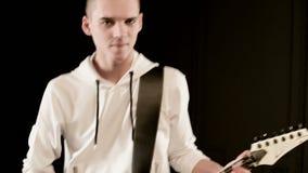 Chitarrista alla moda di ritmo del primo piano con differenti occhi in vestiti bianchi su un gioco nero del fondo espressivo video d archivio