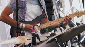 Chitarrista che gioca una chitarra elettrica in una banda rock durante lo spettacolo dal vivo che mette a fuoco di nuovo ai prece video d archivio