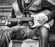 Chitarrista con una chitarra elettrica variopinta nel b&w Immagini Stock