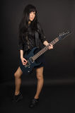 Chitarrista della ragazza con la sua chitarra su un fondo nero Fotografia Stock