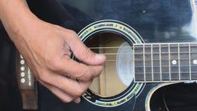 Chitarrista maschio che strimpella chitarra Chiuda su, profondità di campo bassa video d archivio