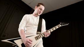 Chitarrista solo alla moda con i dreadlocks sulla sua testa ed in vestiti bianchi su un gioco nero del fondo espressivo video d archivio