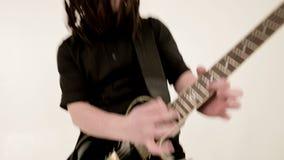 Chitarrista solo alla moda con i dreadlocks sulla sua testa ed in vestiti neri su un gioco bianco del fondo espressivo video d archivio