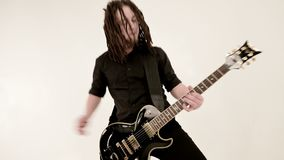 Chitarrista solo alla moda con i dreadlocks sulla sua testa ed in vestiti neri su un gioco bianco del fondo espressivo stock footage