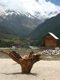 Chitkul village on India China border. Remains of dead tree, wooden hut and snow covered mountains at the village of Chitkul  on the Indian Chinese border Stock Photo