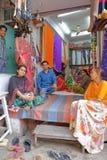 CHITTORGARH RAJASTHAN, INDIEN - DECEMBER 13, 2017: Ståenden av att le kunder och säljare i ett tyg shoppar i den gamla staden Royaltyfria Bilder