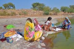 CHITTORGARH, RAJASTHAN, INDIEN - 13. DEZEMBER 2017: Porträt von drei Frauen Kleidung waschend und mit bunten Sari nahe bei geklei lizenzfreie stockbilder