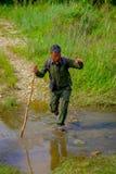 CHITWAN,尼泊尔- 2017年11月03日:使用横渡一根木的棍子的旅游指南一个水坑在森林里在Chitwan 库存照片