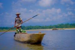 CHITWAN,尼泊尔- 2017年11月03日:未认出的在木小船独木舟的人乘独木舟的徒步旅行队在Rapti河 免版税库存图片