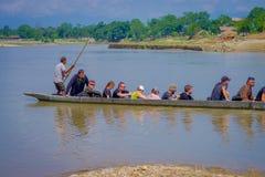 CHITWAN,尼泊尔- 2017年11月03日:未认出的在木小船独木舟的人民乘独木舟的徒步旅行队在Rapti河,  免版税库存照片