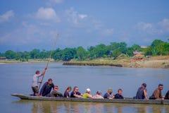 CHITWAN,尼泊尔- 2017年11月03日:未认出的在木小船独木舟的人民乘独木舟的徒步旅行队在Rapti河,  库存照片