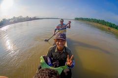 CHITWAN,尼泊尔- 2017年11月03日:未认出的在木小船独木舟的人民乘独木舟的徒步旅行队在Rapti河,  库存图片