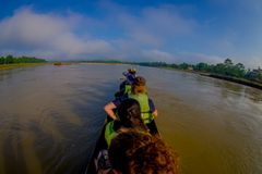 CHITWAN,尼泊尔- 2017年11月03日:未认出的在木小船独木舟的人民乘独木舟的徒步旅行队在Rapti河,  免版税图库摄影