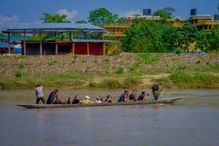 CHITWAN,尼泊尔- 2017年11月03日:未认出的在木小船独木舟的人民乘独木舟的徒步旅行队在Rapti河 图库摄影