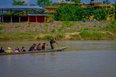 CHITWAN,尼泊尔- 2017年11月03日:未认出的在木小船独木舟的人民乘独木舟的徒步旅行队在Rapti河 免版税图库摄影